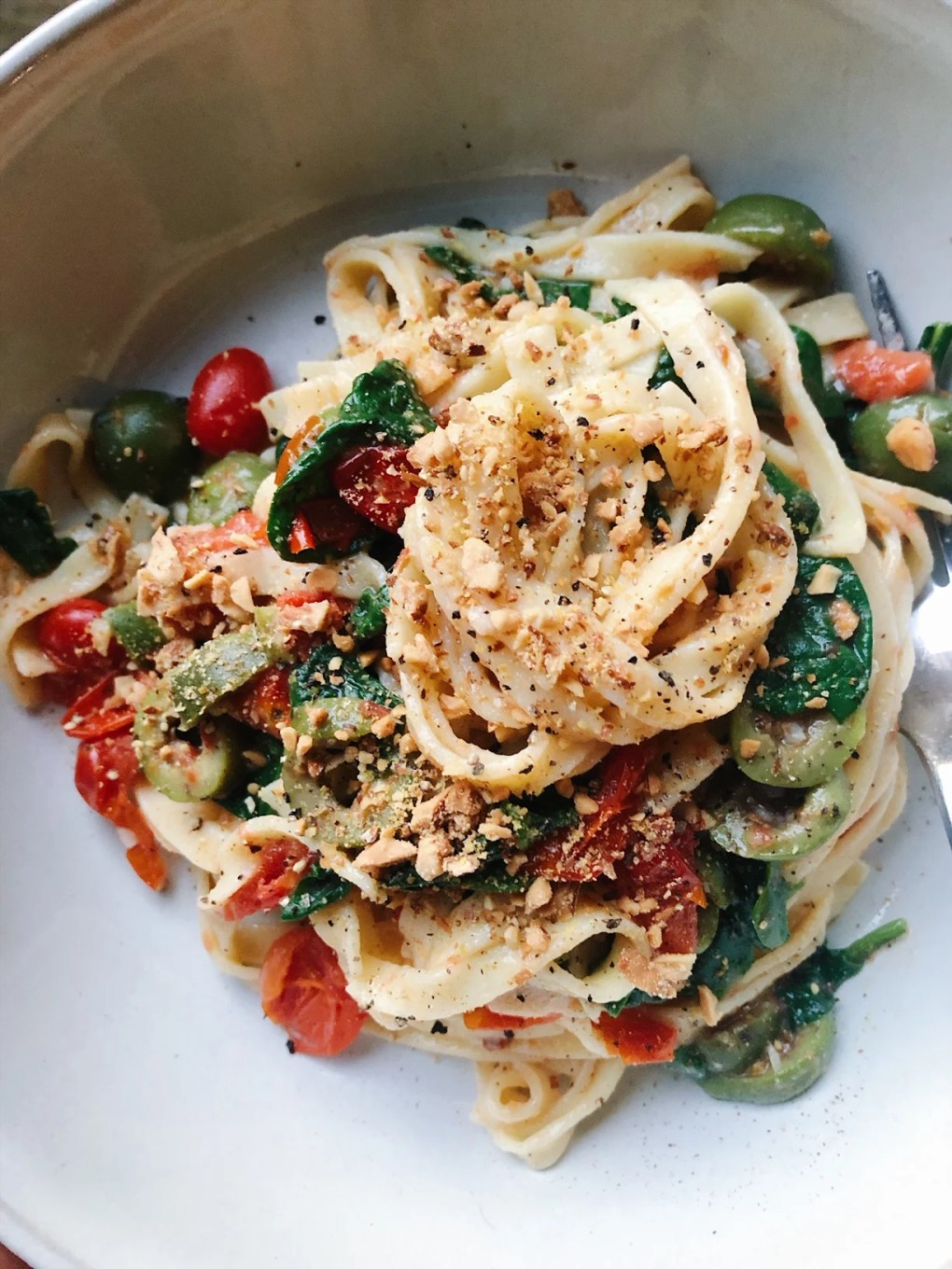 "A bowl of almond flour fettuccine pasta with cherry tomatoes, spinach, and olives. Topped with toasted almond ""parmesan"" cheese in a big white bowl"