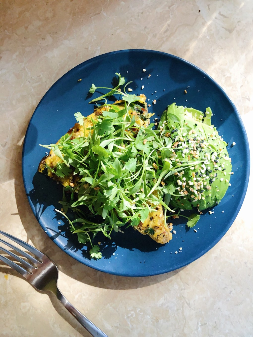 Frittata on a blue plate with avocado, microgreens, and everything but the bagel spice