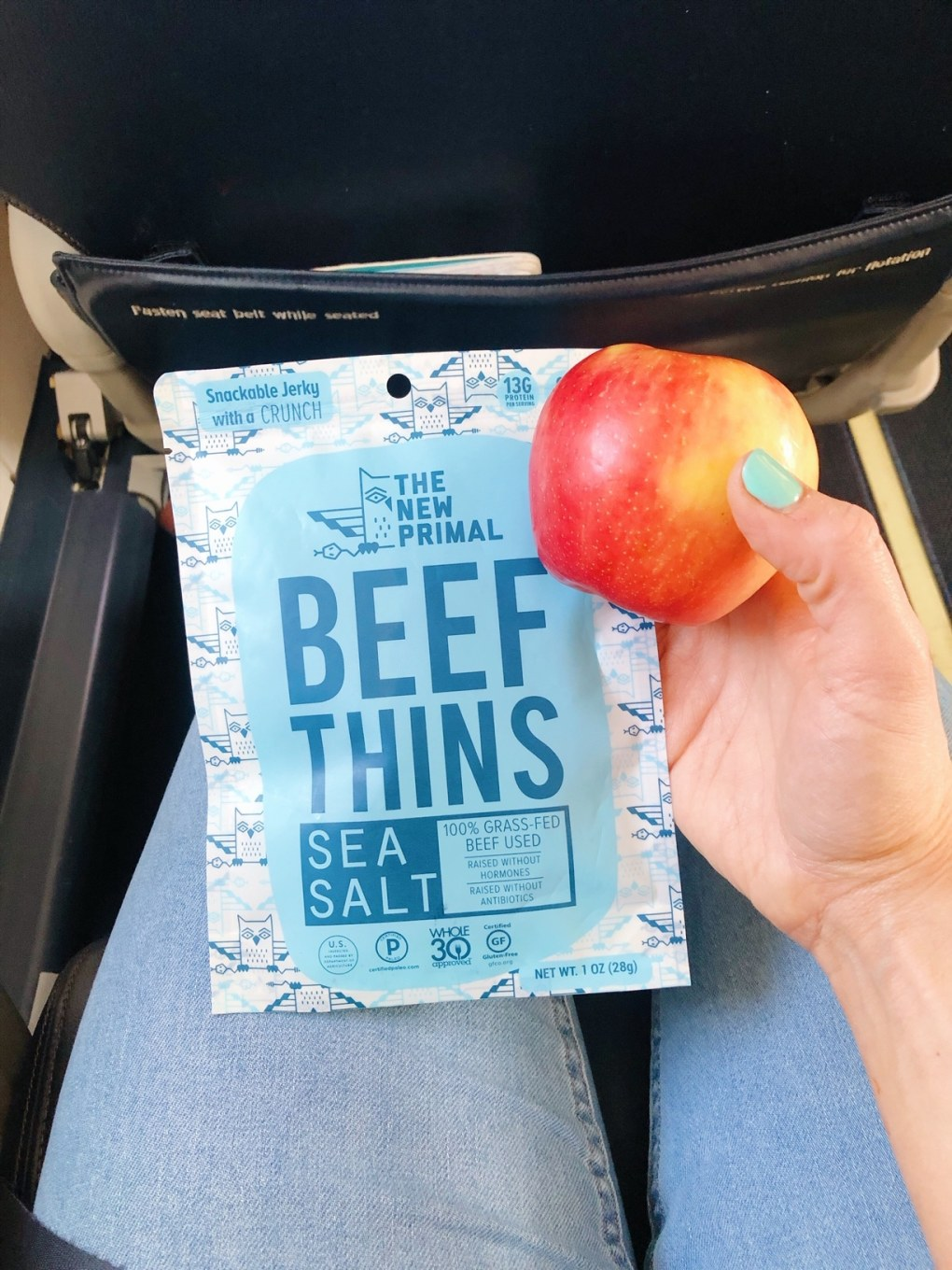 Holding a bag of the new primal beef thin snacks and an apple in my lap on an airplane