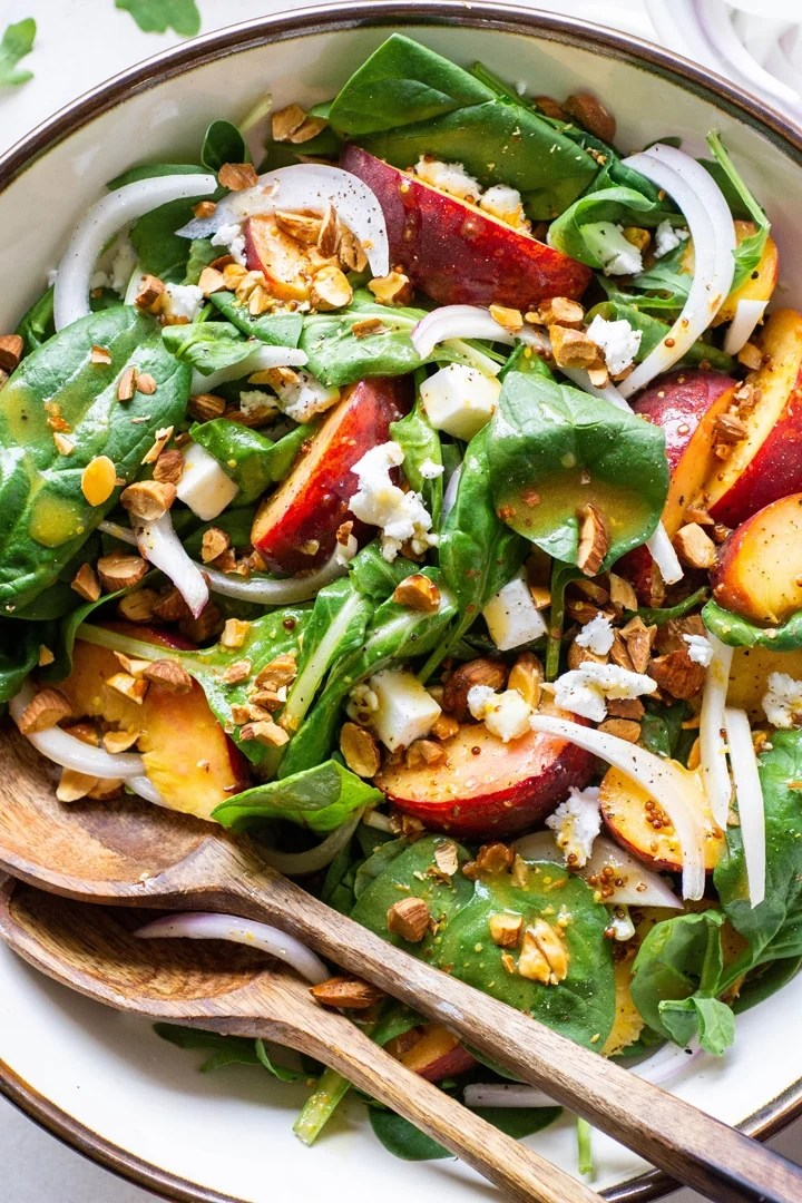 Close up view of a green salad with peaches, chopped almonds, sliced onion, and crumbled feta cheese with mustard dressing
