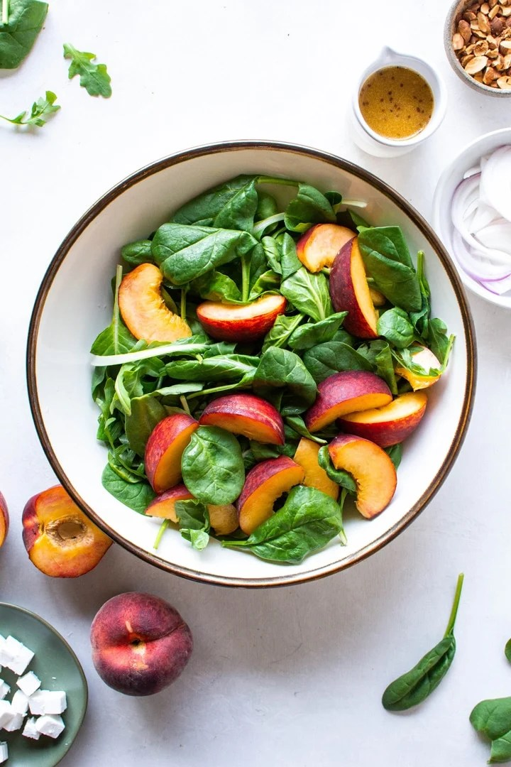 A large bowl of salad greens and sliced peaches on a light colored background surrounded by halved peaches, and a small bowl of red onions.
