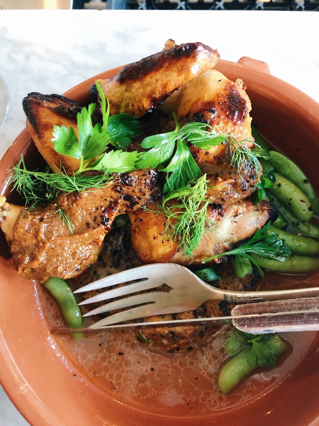 Roasted Chicken in a large bowl over a rice cake with fresh herbs on a white marble counter