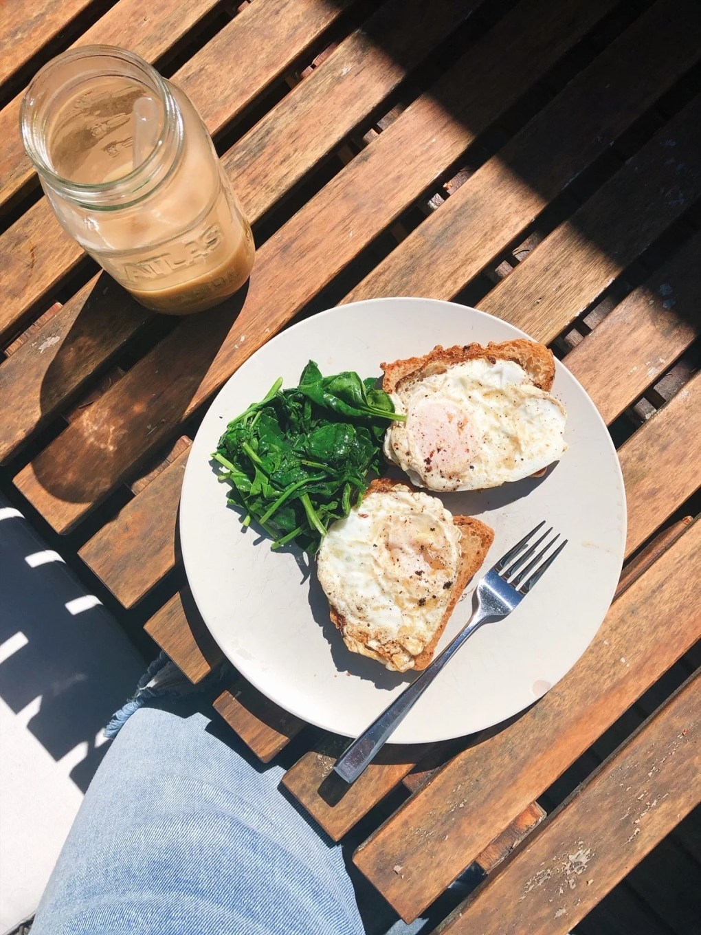 A plate on an outdoor wooden table with two open faced fried egg sandwiches and a side of sauteed spinach