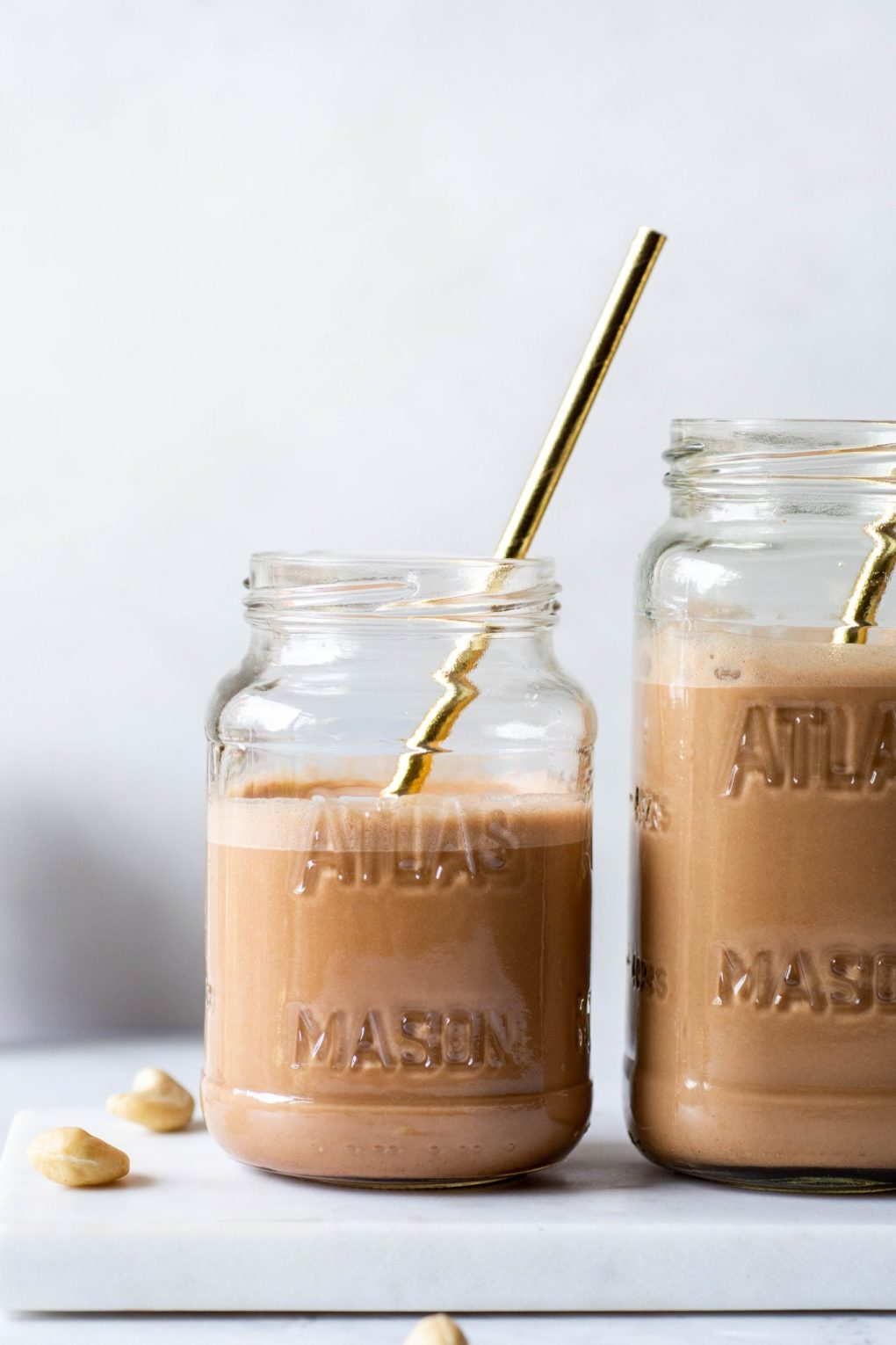 Close up side angle shot of two mason jars of chocolate cashew milk with gold straws on a white background