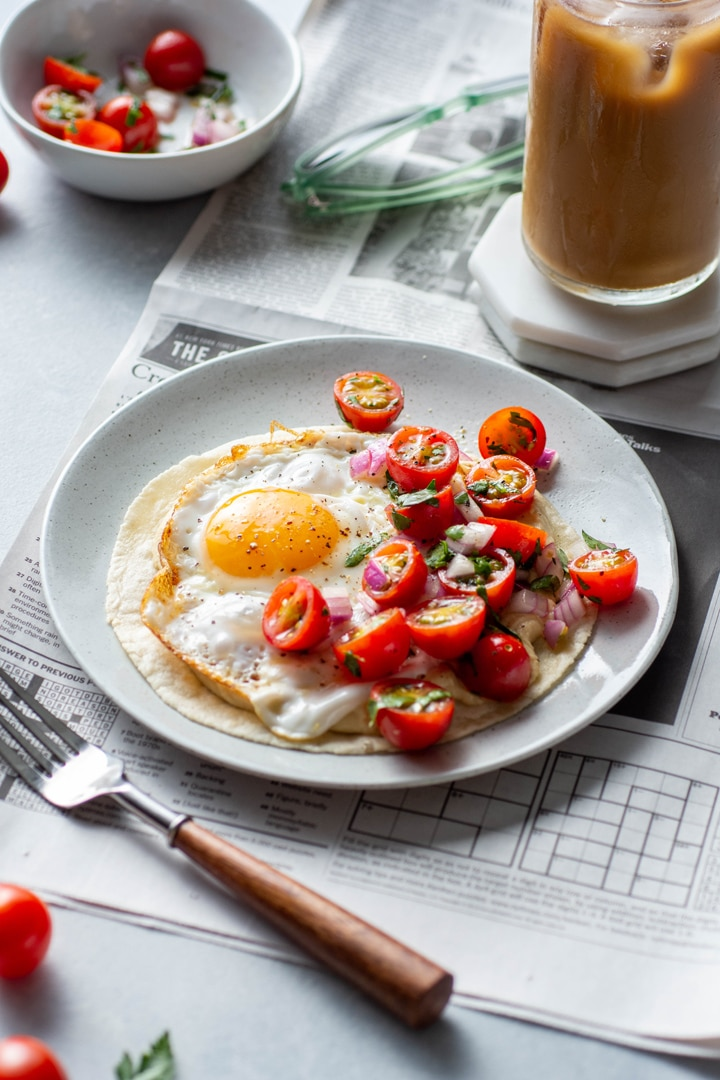 Side angle of a plate with open faced fried egg and hummus breakfast taco topped with a simple tomato salad. Sitting on top of a newspaper on a light colored background next to an iced coffee and some cute sunglasses.