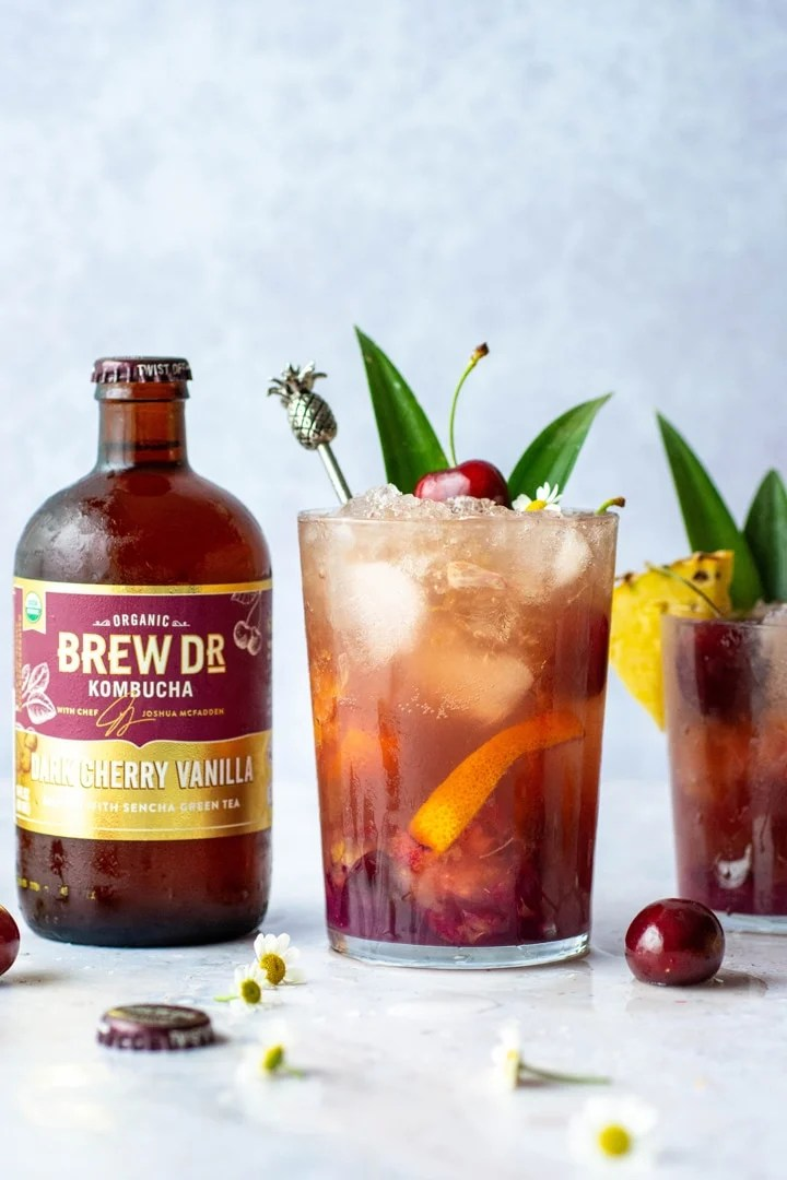 A tropical kombucha cocktail with pineapple leaves and a cherry on a light blue background next to a bottle of Brew Dr. Kombucha