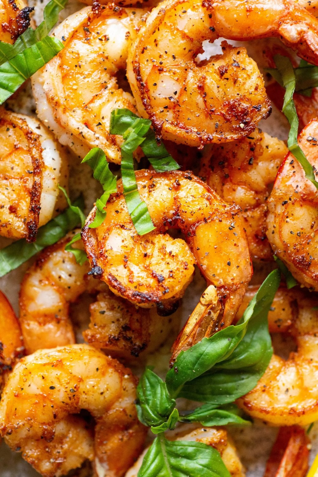 Close up shot of seared shrimp topped with fresh basil