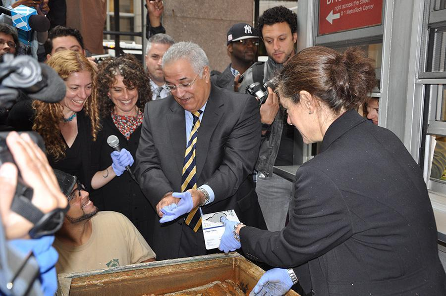 Carmen Bianco, president of New York City Transit, puts on gloves before picking up the artifacts.