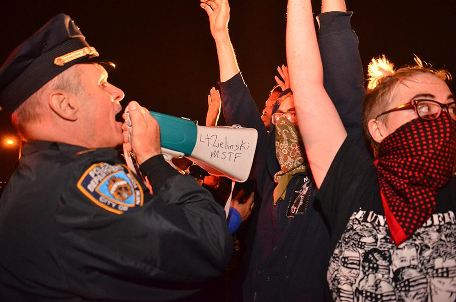 A police officer yells at protesters.