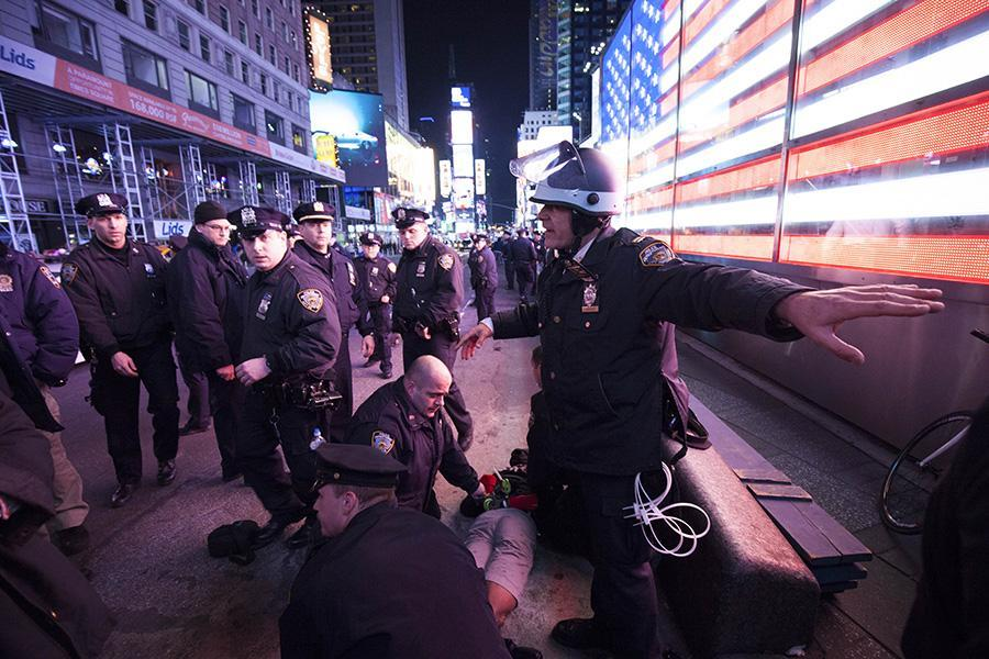 Police officers arrest a man in Times Square.