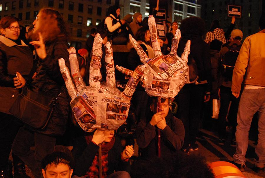Protesters hold up newspaper sculptures of hands on Tuesday.