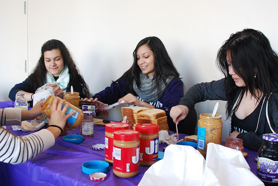 Sarah Vaz, Sohanna Islam and Shela Wu, left to right, make peanut butter and jelly sandwiches for Bowery Mission in Kimmel on Monday.