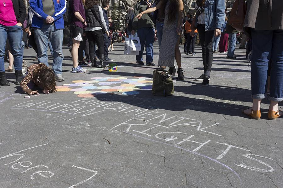 Lila Bales, 6, chalks in the middle of a rally in Washington Square Park on Saturday.