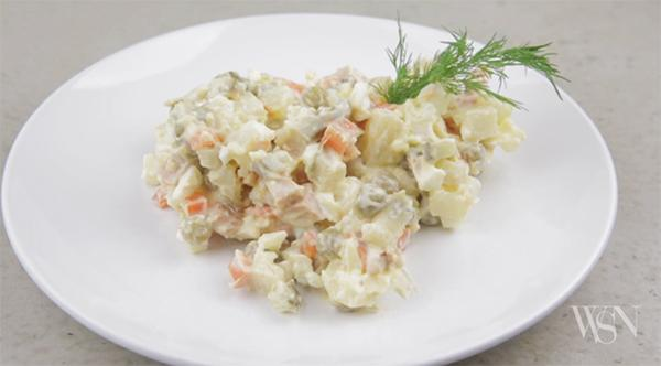 Traditional Russian dish, Olivier Salad is best served with a garnish of dill.
