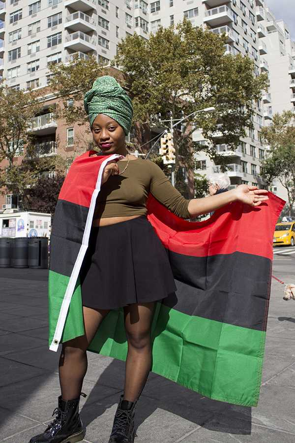 Chioma Nwana, president of NYU's African Students Union, is wearing a traditional Nigerian headscarf and holding the Pan-African flag.