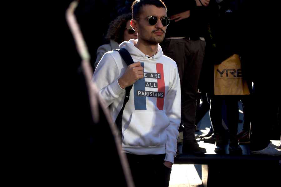 A young man watches on, wearing a sweatshirt to show his solidarity with the people of Paris.
