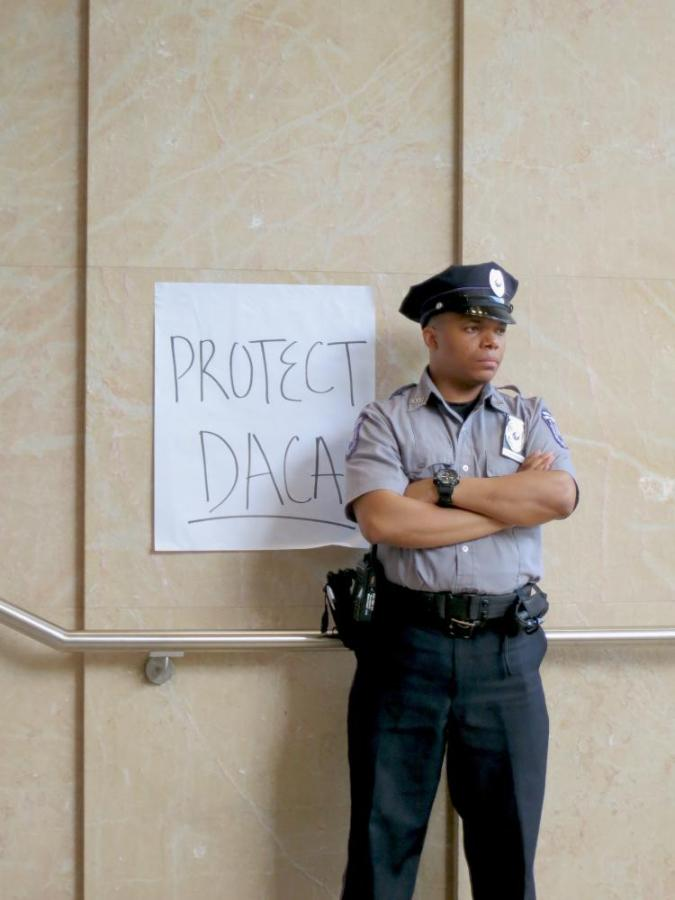 A security officer looks on over the crowd of protesters in Kimmel.