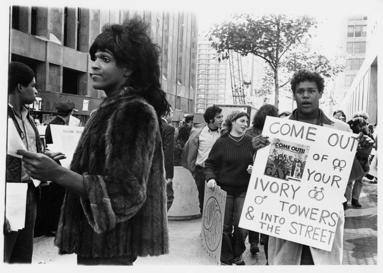 The photo depicts Marsha P. Johnson, an African-American gay liberation activist, handing out flyers in support of queer students at NYU outside of Weinstein Residence Hall in 1970.