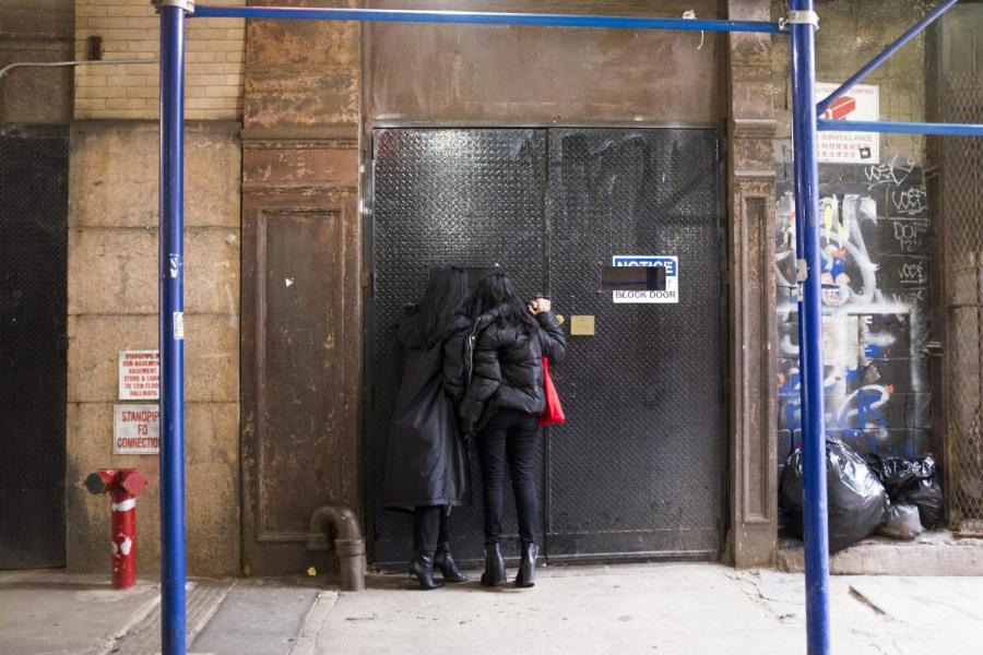 Two visitors peek inside Mmuseumm, located on Cortlandt Alley. Even when the museum is closed, visitors can call a toll-free number to hear about the objects, or look inside the building's windows. (Photo by Katie Peurrung)