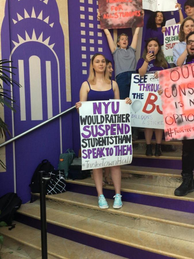 On the steps inside the Kimmel Center for University Life, a student activist holds a sign that reads,