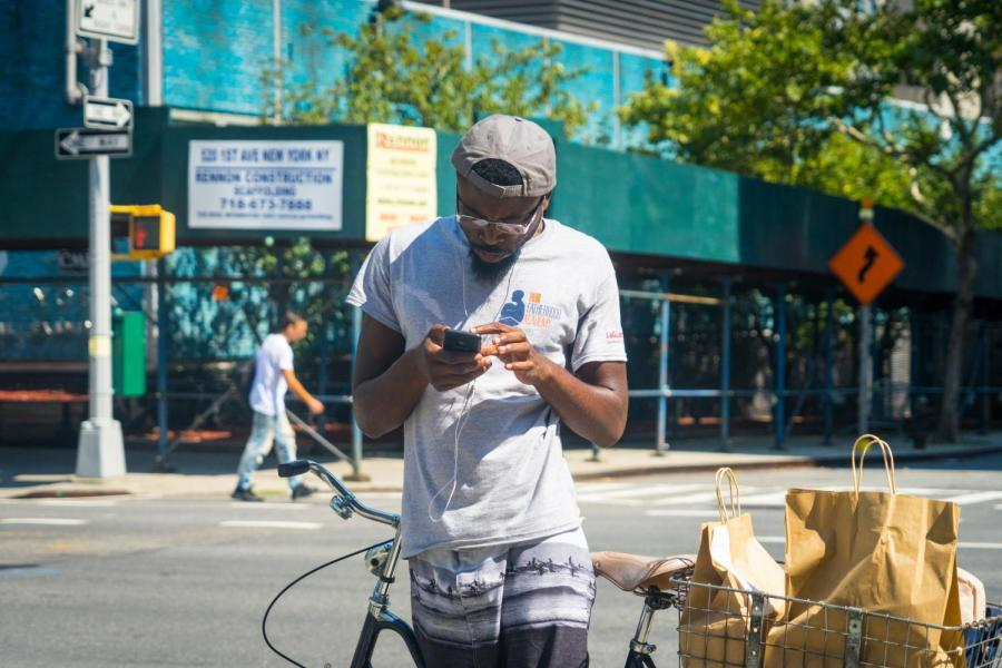 A man uses earbuds on a street corner.