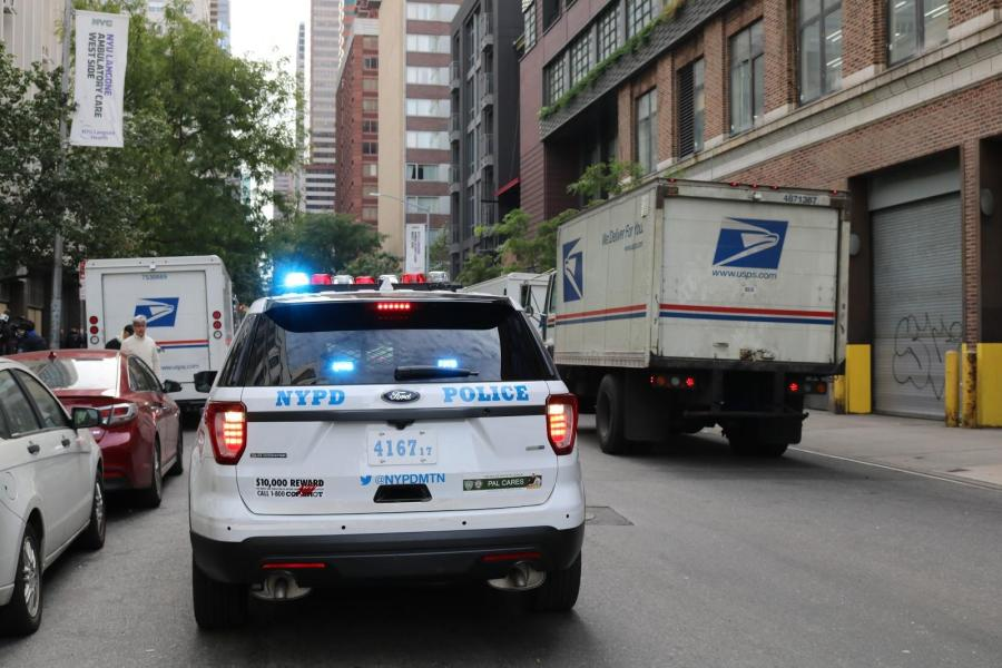 A police car weaves between US Postal Service vans nearby NYU Langone's emergency care unit.