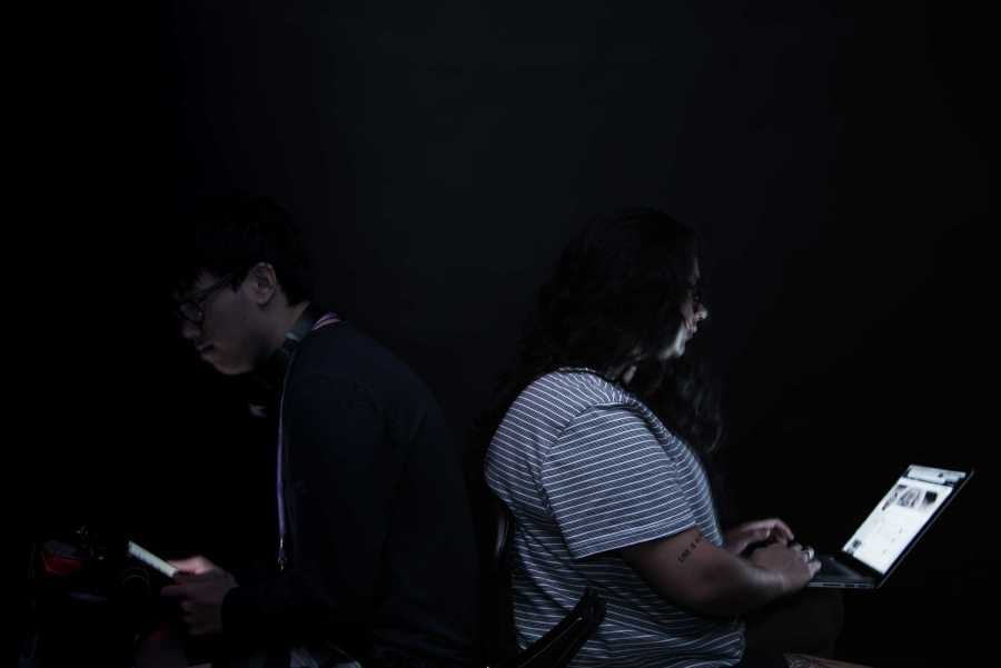 Tisch sophomore Brian Cheng (left) and Stern junior Dani Velasquez (right) sit back-to-back illuminated by phone and laptop screens, respectively. (Photo by Sam Klein)