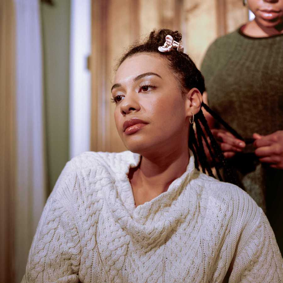 Winter has her hair braided in her apartment while wearing a sweater knitted in the weaving pattern of her family's clan from Ireland. (Photo by Alina Patrick)