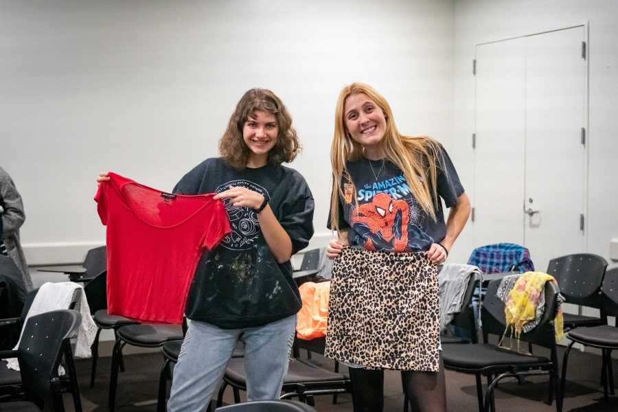 Gabrielle Mendelssohn (left) and Lilly Ferris, Co-Presidents of EarthMatters@NYU, showcasing clothes collected for the Clothing Swap. Mendelssohn and Ferris both wore clothes they picked up from other zero-waste events. (Photo by Tony Wu)