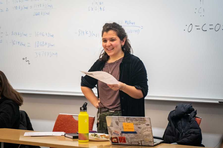 Kat Facchini talks to her colleagues during an NYDM meeting. On Facchini's laptop are stickers from NYU Welcome Week and NYDM. (Photo by Tony Wu)