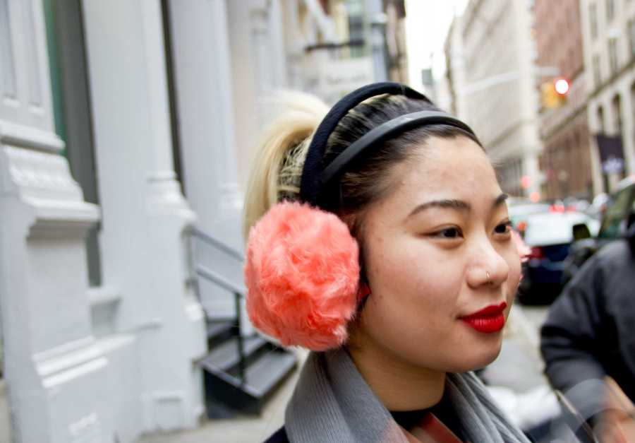 A woman wears coral earmuffs in the streets of SoHo, New York. (Photo by Jorene He)
