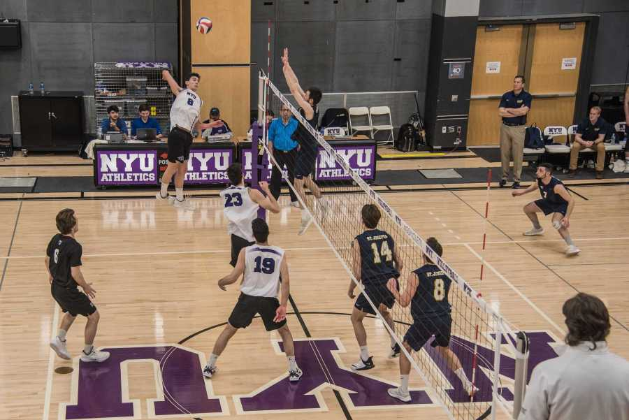 First-year James Haag (8) goes for a kill in a game against St. Joseph's College (L.I.) on Saturday. NYU won the game in four sets, moving their record to 12-8 overall. (Photo by Sam Klein)