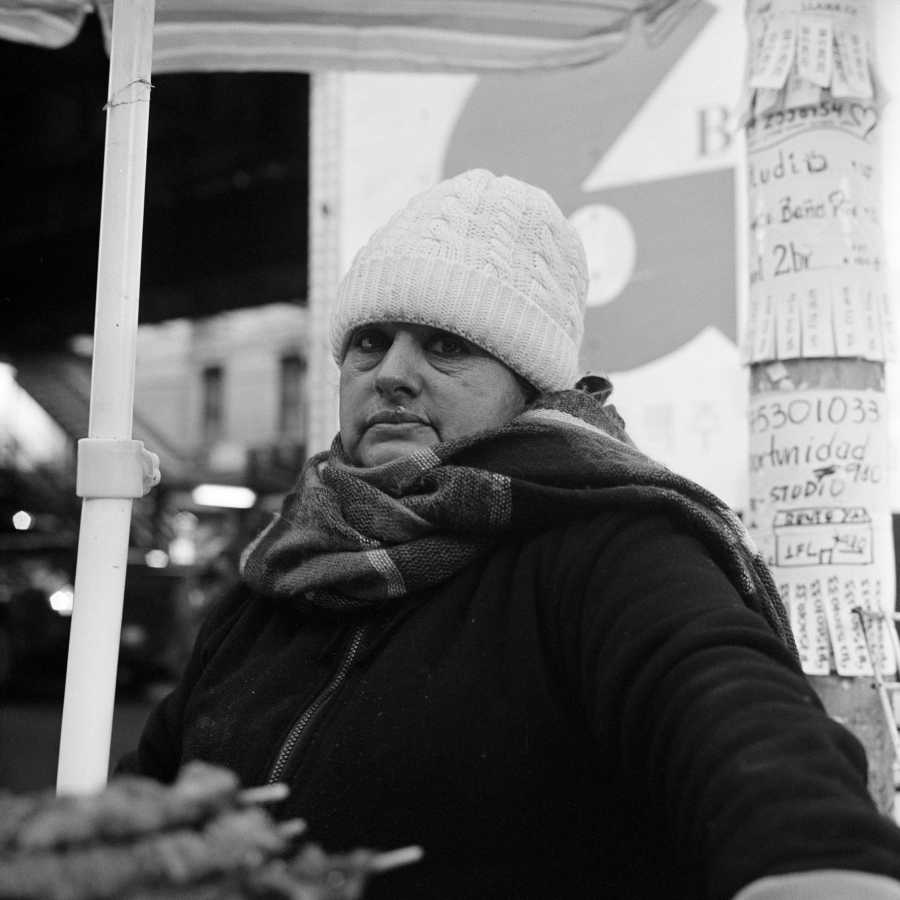 She was working at a food cart, and although she agreed to let me take her portrait, she only glanced up at the camera for a moment. Otherwise, she stared at the ground. She never smiled.