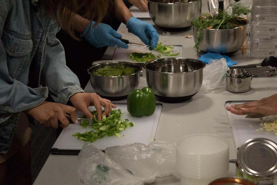 A student cuts a green pepper to be used in the spaghetti sauce. (Photo by Victor Porcelli)