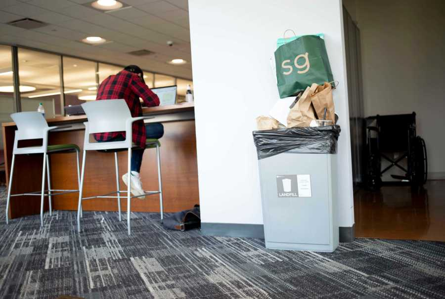 A trash bin overflows with food scraps, containers and papers in Kimmel's seventh-floor student lounge. Some of these items could be recycled. (Staff Photo by Katie Peurrung)