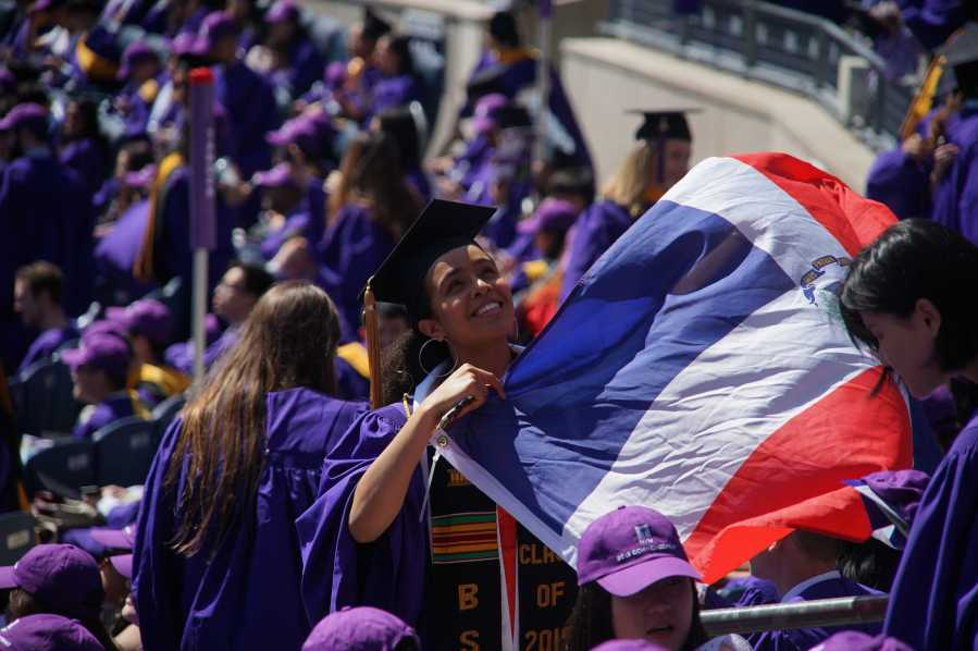 An NYU graduate holds up the Dominican Republic flag while in the stands at Yankee Stadium. The Class of 2020 commencement has been delayed due to the coronavirus pandemic. (Photo by Alana Beyer)