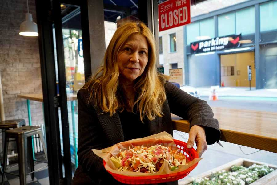 The owner of Dorado Tacos holds up the restaurant's tacos. (Staff Photo by Min Ji Kim)