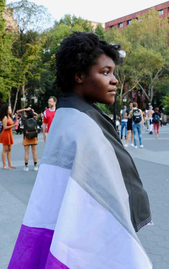 Tisch drama sophomore Journey Brown-Saintel stands in Washington Square Park with the asexual flag wrapped around her body. (Photo by Sara Miranda)