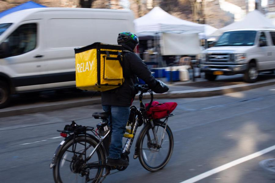 A food delivery bike speeds down a Manhattan street. The New York City Council is considering regulatings food delivery apps such as GrubHub and Postmates. (Photo by Richard Chen)