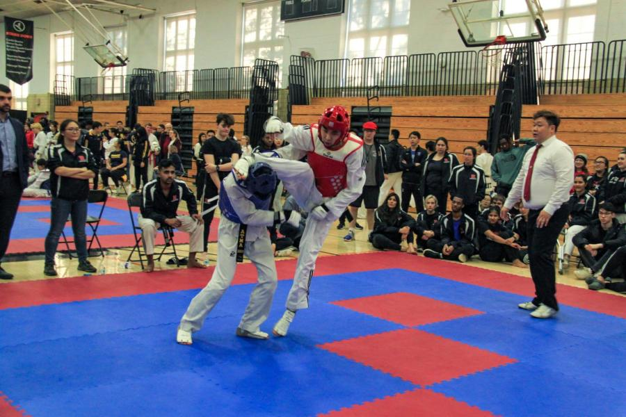 Tandon junior and NYU Taekwondo team captain Jonathan Ahn sparring in red gear scores three points with a headshot against a Rutgers opponent at the Princeton tournament in March. (Staff Photo by Alexandra Chan)