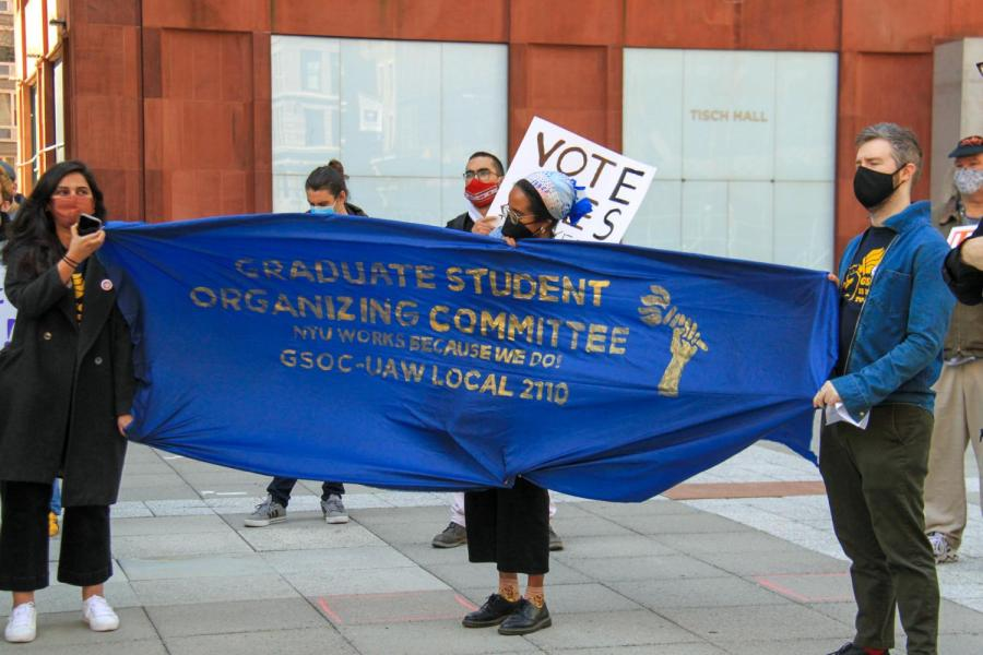 GSOC members hold up a banner at Gould Plaza. (Staff Photo by Alexandra Chan)