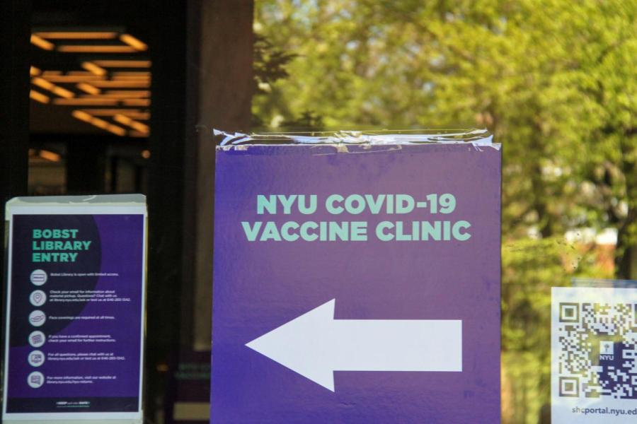 Signs directing students towards an NYU vaccine clinic decorate the front of Bobst Library. NYU students picked for the vaccine lottery gladly collect their doses.  (Staff Photo by Alexandra Chan)