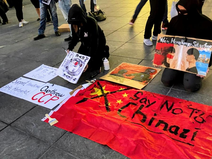 """NYU's Hong Kong Student Advocacy Group displays artwork based on their experiences to spread awareness of the Chinese Government's mistreatment of Hong Kong. The group hosted """"Students for Hong Kong Action Day"""" at Washington Square Park in solidarity with pro-Democracy Hong Kongers. (Staff Photo by Gillian Blum)"""