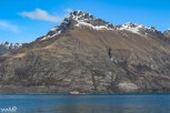 A catamaran sails along Lake Wakatipu below Walter Peak.