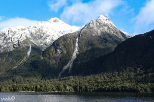 """We had planned on visiting Milford Sound, but the day that we planned to go, a sizeable snow storm brought meters of snow and avalanches to the Milford Road. Instead, we switched our trip to Doubtful Sound, and we were not disappointed! The journey to Doubtful Sound takes you first across Lake Manapouri by boat. Here is one of the views from on the lake. The streaks on the mountains, we were told, were likely """"tree avalanches."""" Loose trees fall and take all the other trees below them."""
