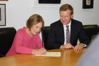 Kristine Bartlett signs the terms of the offer with Health Minister Jonathan Coleman