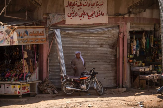 Un iraquí continúa frente a una tienda cerrada en el oeste de Mosul