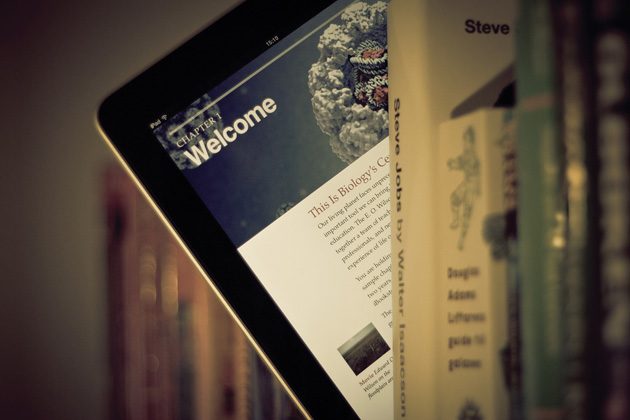 iPad with a textbook peeks out from a library