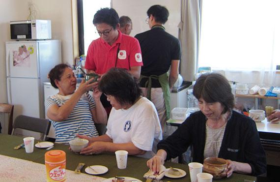 参加者の方々に抹茶をお渡しするAARの高木卓美