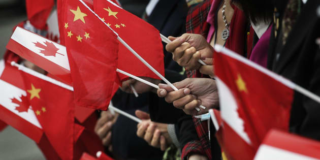 People gather holding Chinese and Canadian flags in Vancouver, B.C.